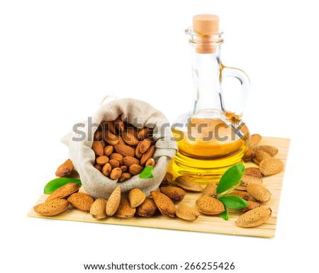 Almonds in the sack, almond oil and green leaves on mat isolated on white background - stock photo