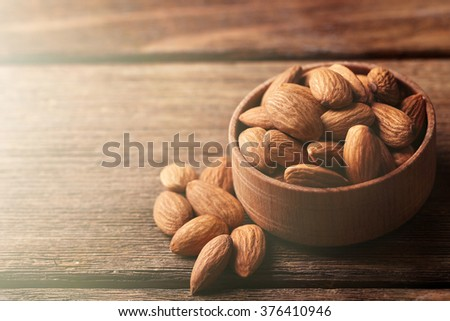 Almonds in the wooden bowl on the table, close-up - stock photo