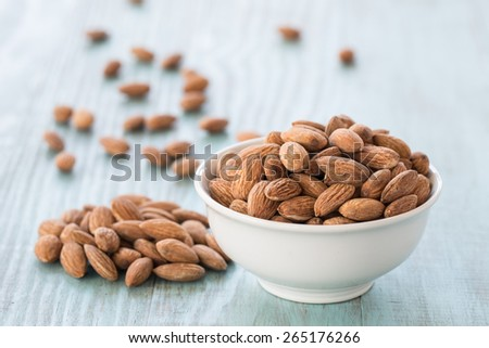 Almonds in white bowl on blue wooden background - stock photo