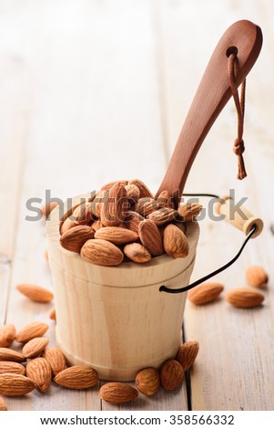 Almonds in wood bucket - stock photo