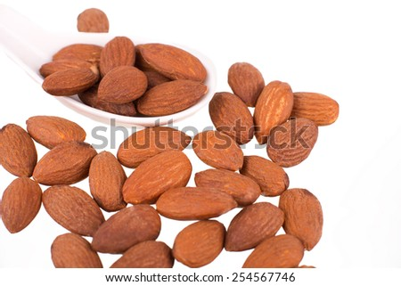 Almonds kernel in a wooden plate,  isolated on white background - stock photo