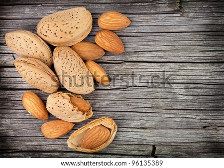 Almonds nuts on the wooden texture - stock photo