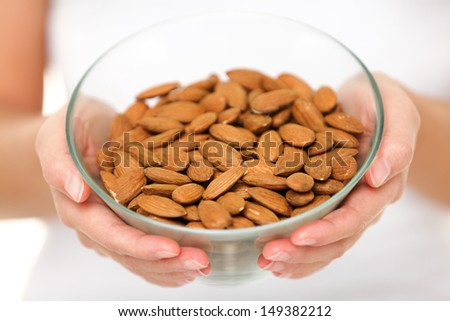 Almonds nuts - woman showing raw almond bowl close up. Healthy food concept in studio with hands lifting bowl of unprocessed almonds isolated on white background.