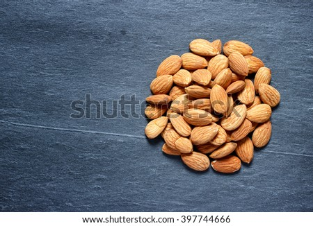 almonds on a natural dark stone background
