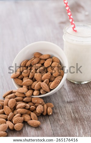 Almonds spilling out of white bowl onto wood background with glass of almond milk with heart straw - stock photo