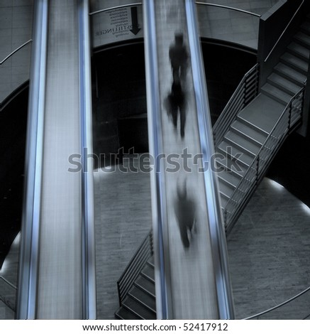 Almost abstract composition of moving stairs crossing the interior of the Royal Library in Copenhagen with people moving on and being blurred - stock photo