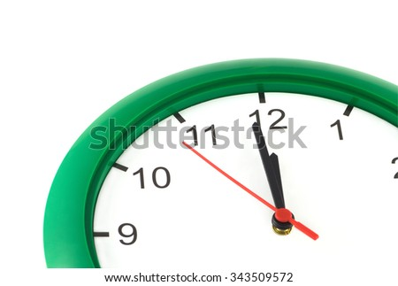Almost twelve o'clock on part of big wall clock in green case isolated on white vertical view closeup - stock photo