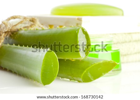 Aloe vera cosmetics: cream, aloe vera plant, soap and green towel isolated on white background - stock photo