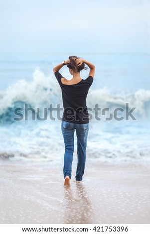 Alone beautiful woman standing in the sea during storm. Relax concept - stock photo