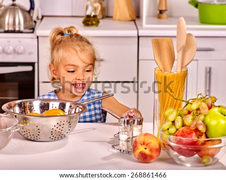 Alone child with rolling-pin dough at home kitchen. - stock photo
