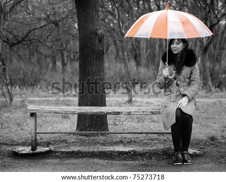 Alone girl sitting at bench in rainy day. Photo in black style.