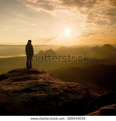 Alone hiker on  rock empire watching over the misty and foggy morning valley to Sun. Alone girl hiking. Hot morning sun rays. View over misty morning landscape. Girl stand on sharp peak, enjoy morning