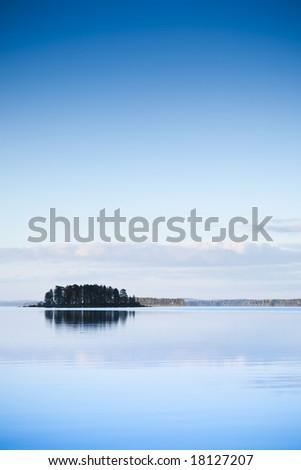 Alone island on the lake at sunset - stock photo