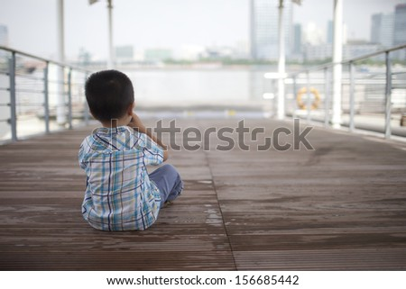 alone little asian boy sitting at the pier