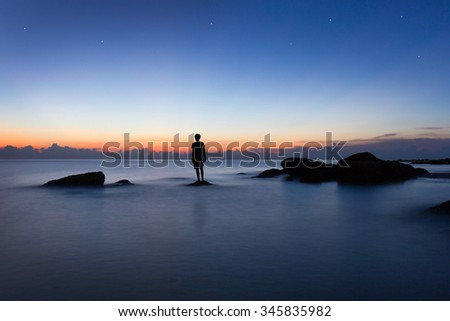 Alone man in sunrise time. Sunrise time. Minimal style. Alone man and silhouette. Silhouette man in landscape. Seascape and sunrise time. Man standing on rock. Beautiful time and nature. Alone man - stock photo