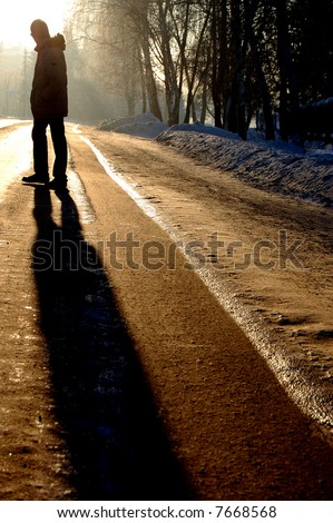 alone silhouette of the guy standing on the winter road - stock photo