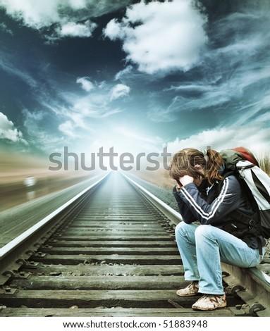 Alone woman sitting on railroad under blue sky - stock photo
