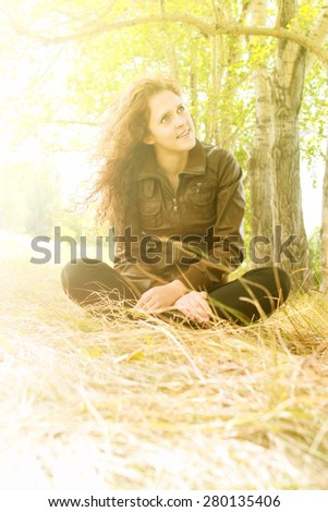 alone Young adult redhead curly woman sit on spring green grass in forest Cute girl look up Female wear casual dark dress Empty space for inscription Windy sunny weather Resting outdoor  - stock photo