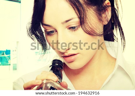 Alone young businesswoman in depression, drinking alcohol - stock photo