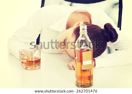 Alone young businesswoman in depression, drinking alcohol. - stock photo