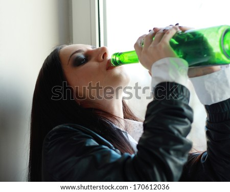 Alone young woman in depression drink alcohol - stock photo