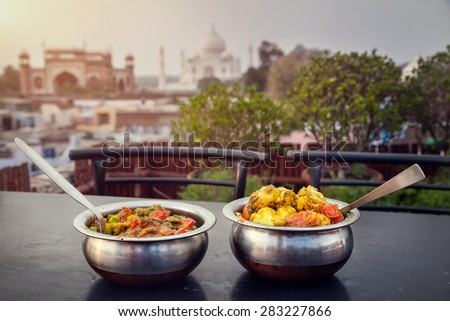Aloo Gobi and Sabji Masala Traditional Indian food in metal plates on rooftop restaurant with Taj Mahal view in Agra, Uttar Pradesh, India - stock photo