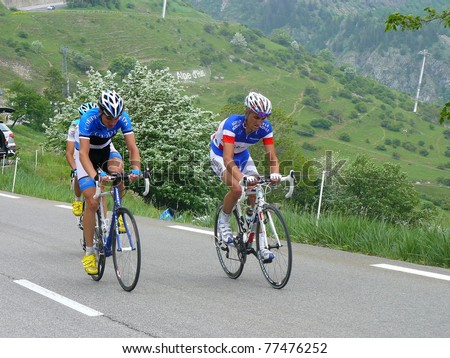 """ALPE D'HUEZ, FRANCE - JUN 12: Professional racing cyclists Estonia and France Champions ride UCI WORLD TOUR """" CRITERIUM DU DAUPHINE LIBERE"""" on June 12, 2010 in Alpe d'Huez pass, Isere, France. - stock photo"""