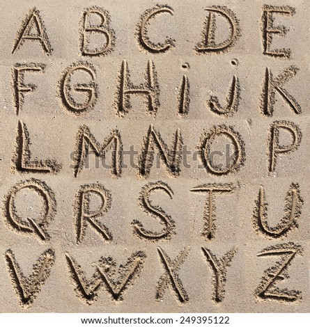 Alphabet (ABC) written on sand. - stock photo