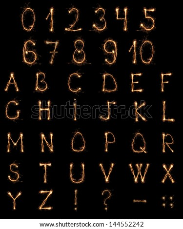 Alphabet and Numbers sparklers on black background - stock photo