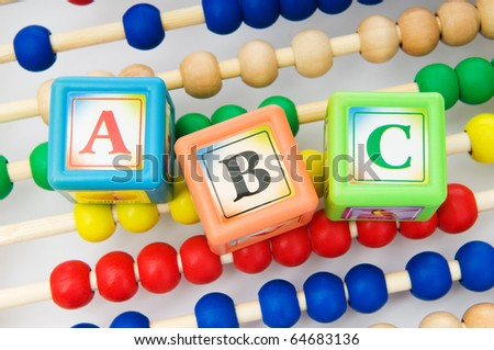 Alphabet blocks and abacus isolated on white - stock photo