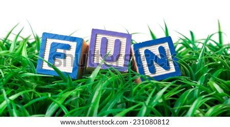 Alphabet blocks forming FUN on a patch of grass  - stock photo