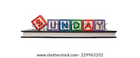 Alphabet blocks forming the word SUNDAY on a book isolated on white background