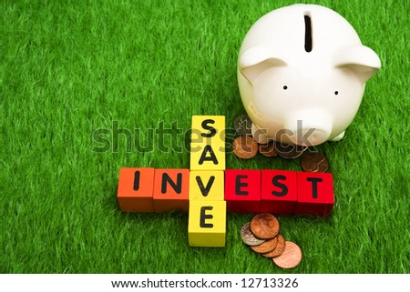 Alphabet blocks spelling save and invest with piggy bank - stock photo