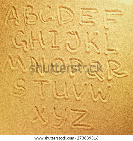 Alphabet letters handwritten in the sand on the beach - stock photo