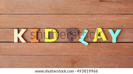 "Alphabet letters ""KID PLAY"" on wood plank. Education concept."