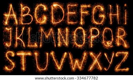 Alphabet made of sparklers isolated on black background - stock photo