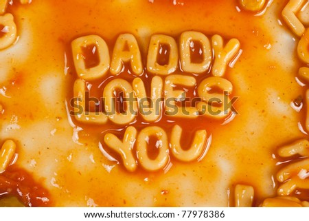 Alphabet shaped pasta forming DADDY LOVES YOU in tomato sauce - stock photo