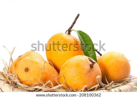 Alphonso Mango kept for ripe in dry grass - stock photo