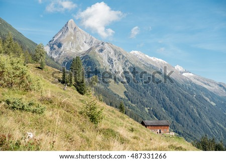 Alpine autumn landscape with mountain peaks and wooden huts