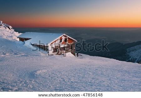 Alpine chalet in sunset - stock photo