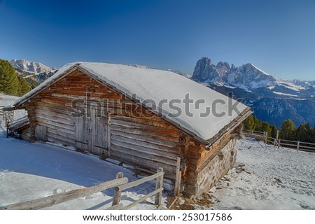 Alpine chalet surrounded by a fence in the snow in front of a panorama of snowy peaks on a bright sunny day in winter - stock photo