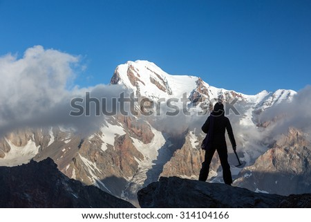 Alpine Climber Reached Summit Silhouette Woman Staying on Top of Rock Cliff Holding Climbing Gear Stormy Clouds and Peaks Illuminated bright Morning Sun - stock photo