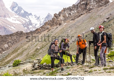 Alpine climbers team and camp. Group of five people men and women staying along green camping tent on majestic mountain landscape of deserted Asian area