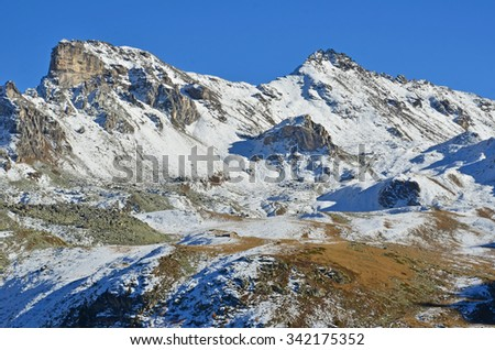 Alpine hut dwarfed by the Medispitz (left) and Rotighorn (right) in the southern swiss alps above Sierre - stock photo