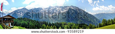 Alpine hut with a flag in the Nature Park Rieserferner-Ahrn in South Tyrol, Italy. Mountains and valleys, blue sky and white clouds; panorama picture Alpine hut in the mountains - stock photo