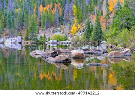 Alpine lake in the fall with yellow and red aspens reflecting in the water