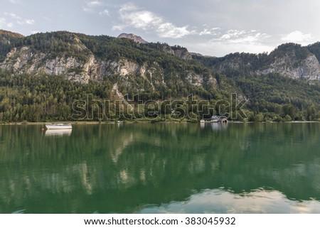 Alpine lake Mondsee autumn sunset landscape with motor boat and boathouse, Austria - stock photo