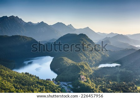 Alpine lakes at sunset - the Alpsee bei Schwangau and the smaller Schwansee among hills and peaks. Photographed from the hills above the Neuschwanstein castle. - stock photo