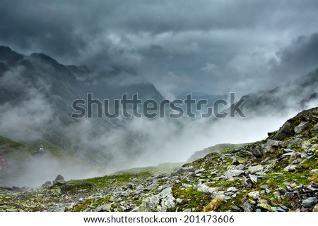 Alpine landscape with mountains and slopes in the mist - stock photo