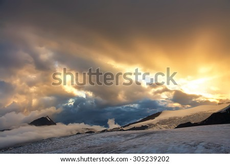 alpine landscape with peaks covered by snow and clouds - stock photo